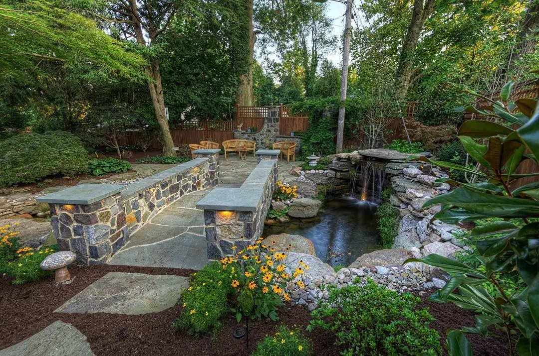 backyard landscaping with nice, straight lines and water feature and bridge photo by Instagram user @disablandscaping