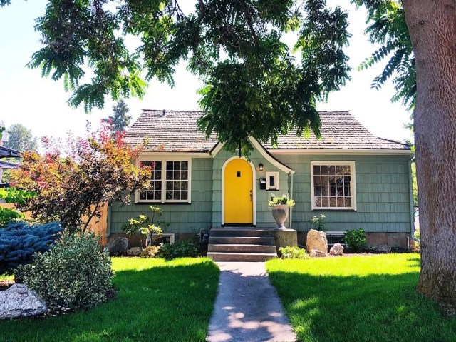 green home with yellow door with large tree in front yard photo by Instagram user @jessicadoss