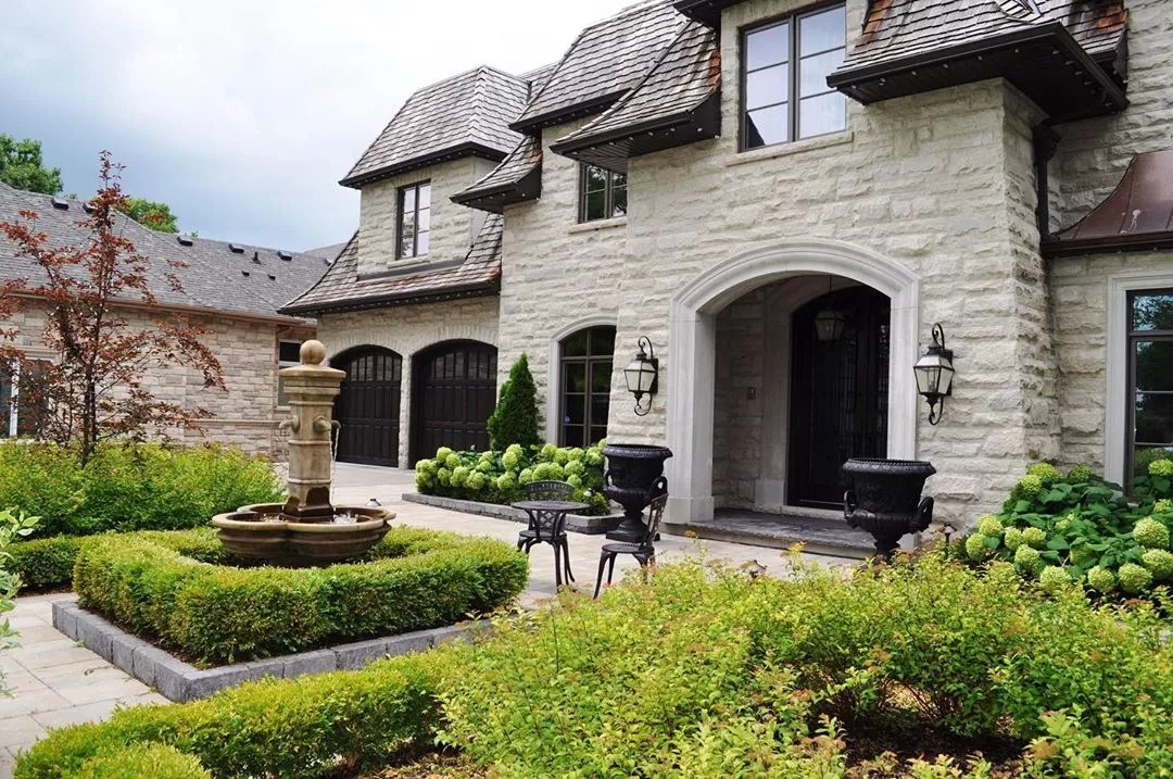 nice stone home with large backyard with a water feature in the center photo by Instagram user @mvklandscapedesign
