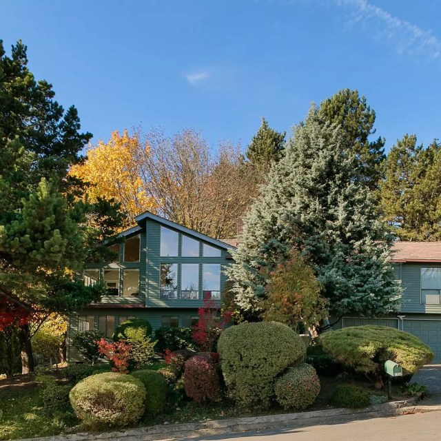 mid-century modern home with green paint and lots of landscaping in front photo by Instagram user @mahaffygroup