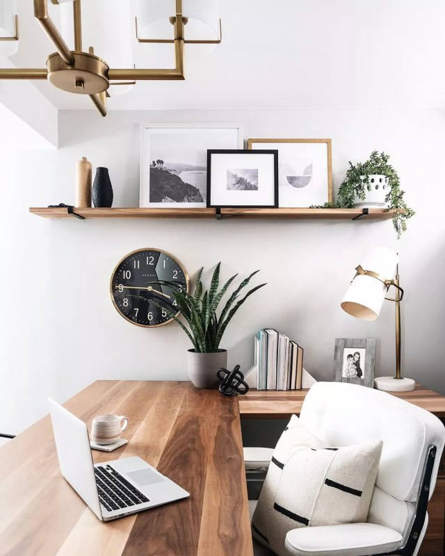 home office space with wodden desk and clock on the wall photo by Instagram user @leclairdecor