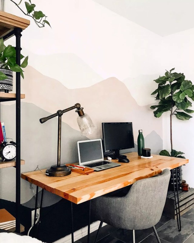 Home office with wood top desk and iron legs and small gray chair and plants photo by Instagram user @thekiwihome