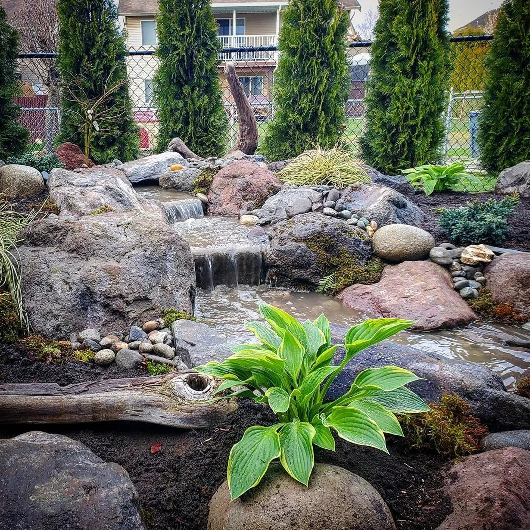 outdoor waterfall built into backyard landscaping photo by Instagram user @fontanawaterfeatures