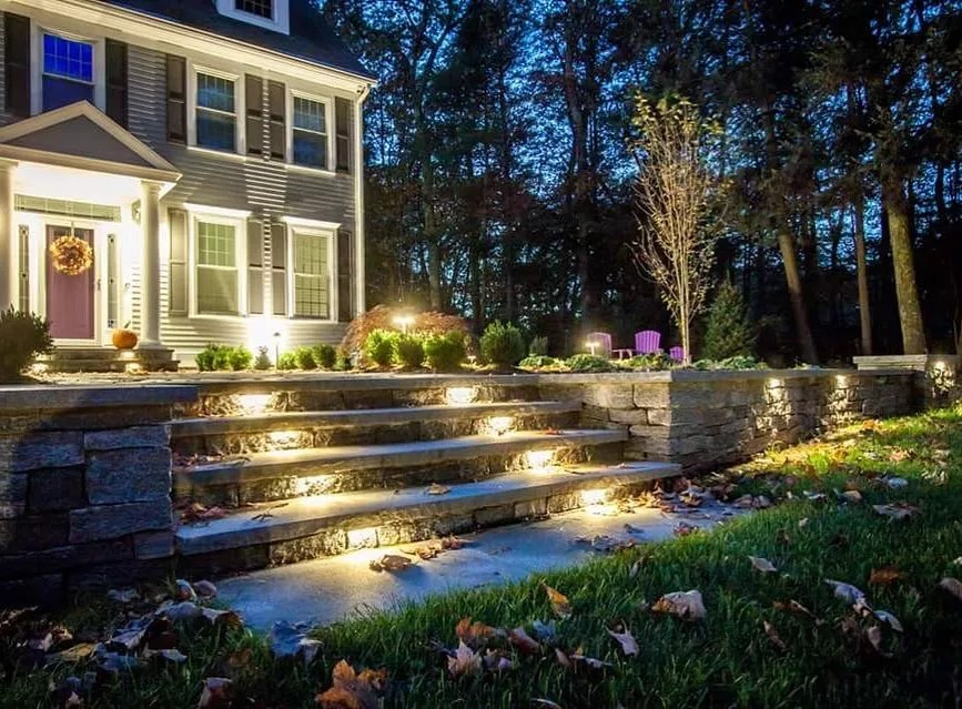 front yard landscaping with steps to front door illuminated by lights built into the light photo by Instagram user @integrallighting