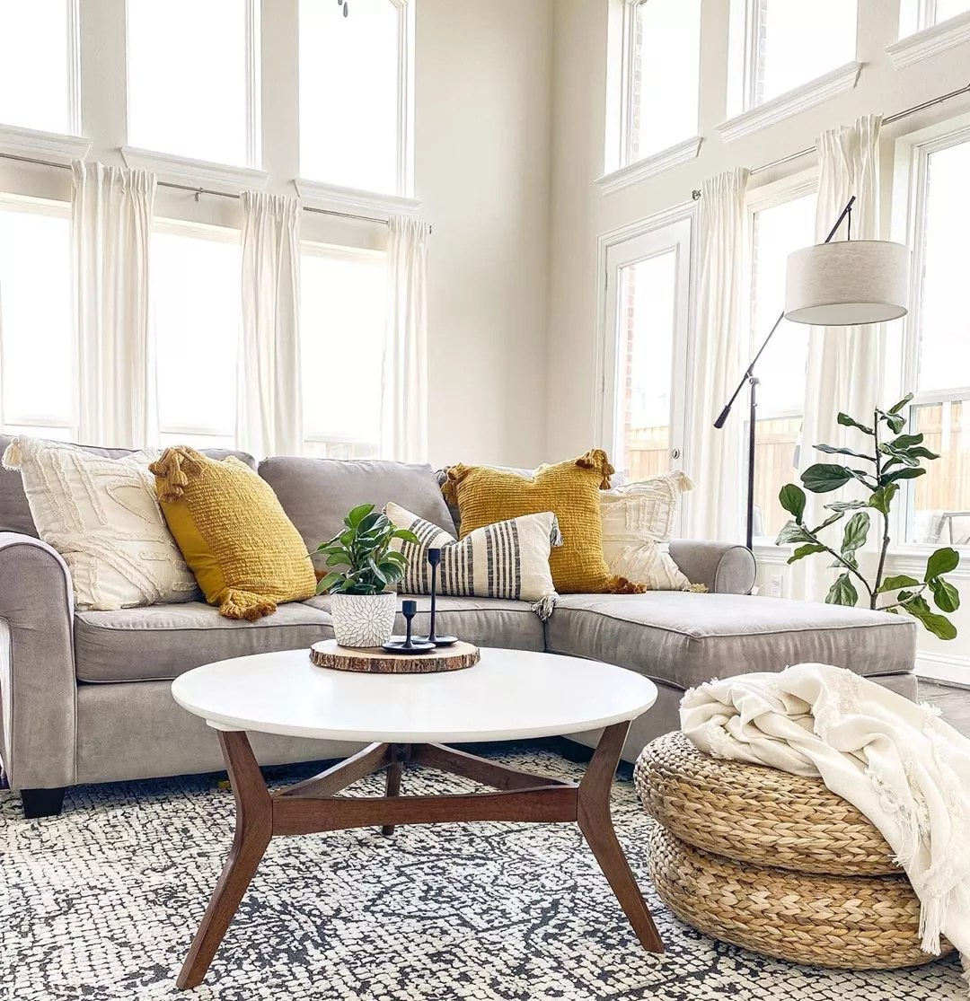 living room space with sectional and area rug with large floor to ceiling windows photo by Instagram user @diariesofmyhome