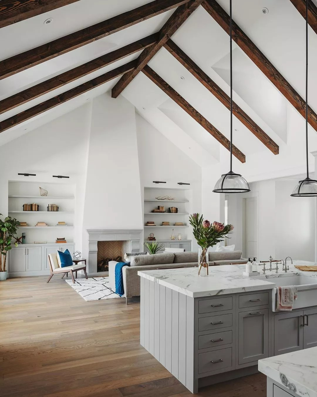 vaulted ceiling over living room and kitchen with wooden beams photo by Instagram user @roehnerryan