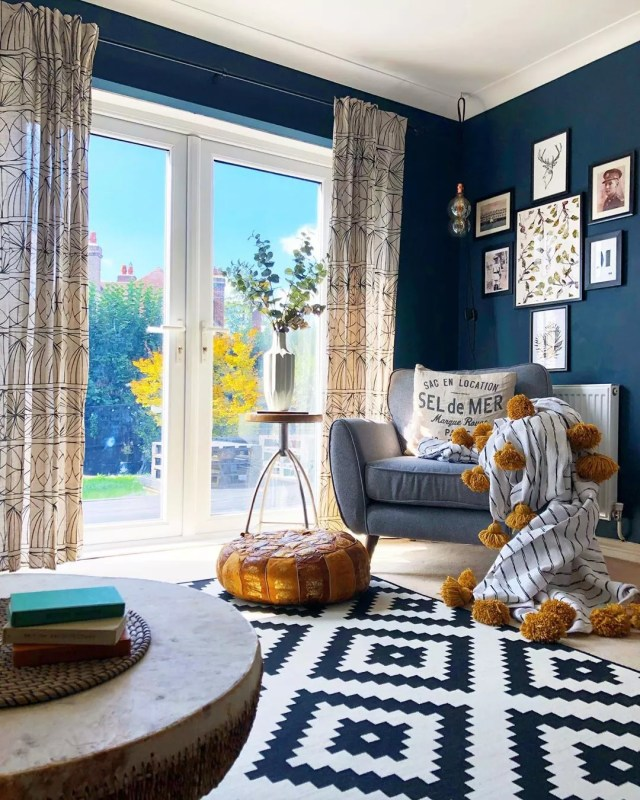 living room with blue walls and white and blue area rug with lots of natural light photo by Instagram user @nest_twenty_eight
