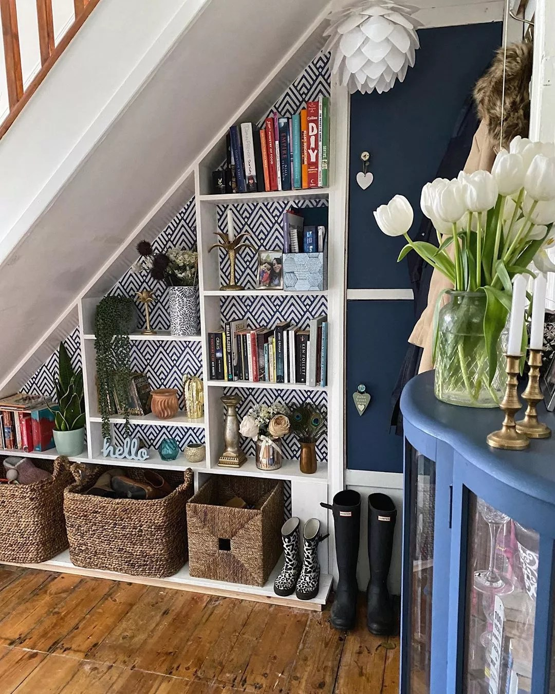 under stair storage space with shelves and woven baskets photo by Instagram user @melaniejadedesign
