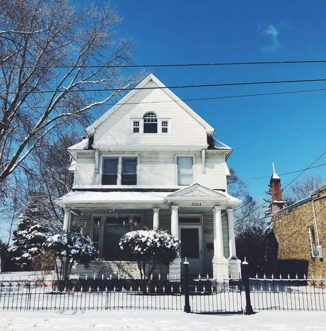 white craftsman style home in minneapolis with snow on the ground photo by Instagram user @northeastminneapolis
