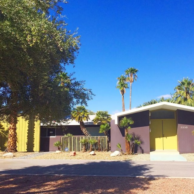 ranch style home with yellow doors and brown siding in Rancho Charleston, Las Vegas photo by Instagram user @eatdrinkhome