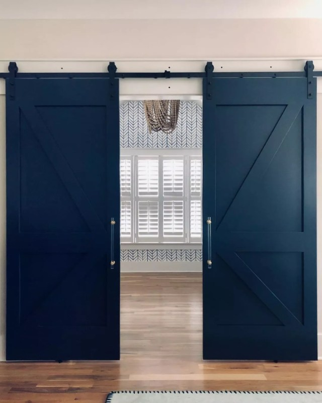 blue barn doors installed in a new home photo by Instagram user @fieldshandcrafted
