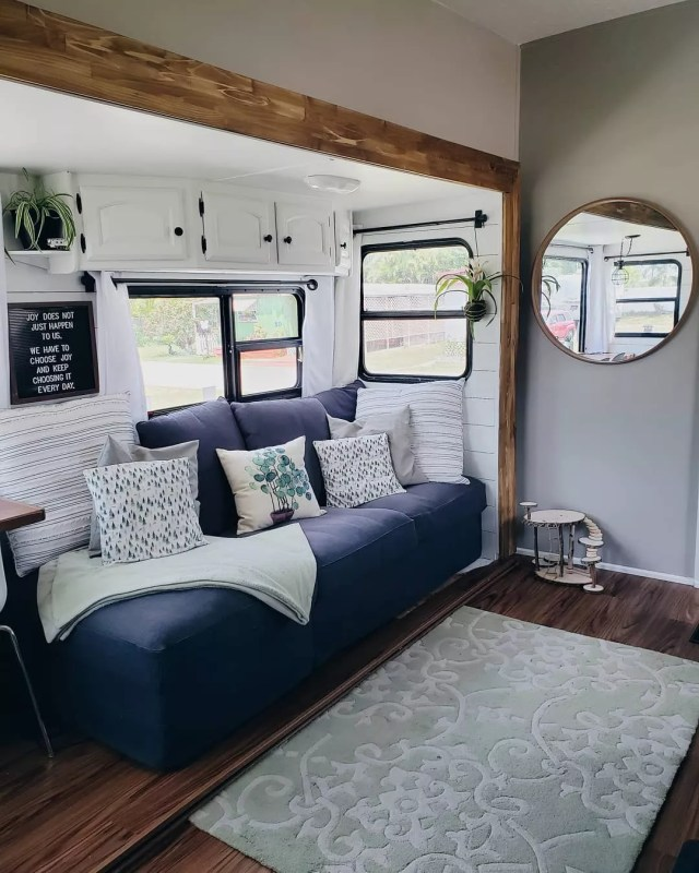 updated RV interior with gray and white walls and a blue couch photo by Instagram user @rvsandtrees