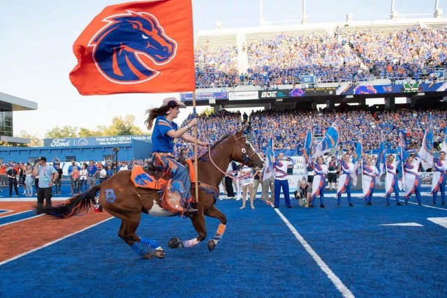 woman riding horse on the blue field at Boise State University photo by Instagram user @boisestateuniversity