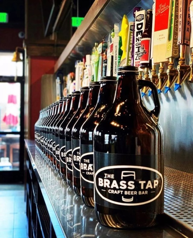 Growlers Lined Up Under Beer Taps at the Brass Tap Bar. Photo by Instagram User @the_brass_tap