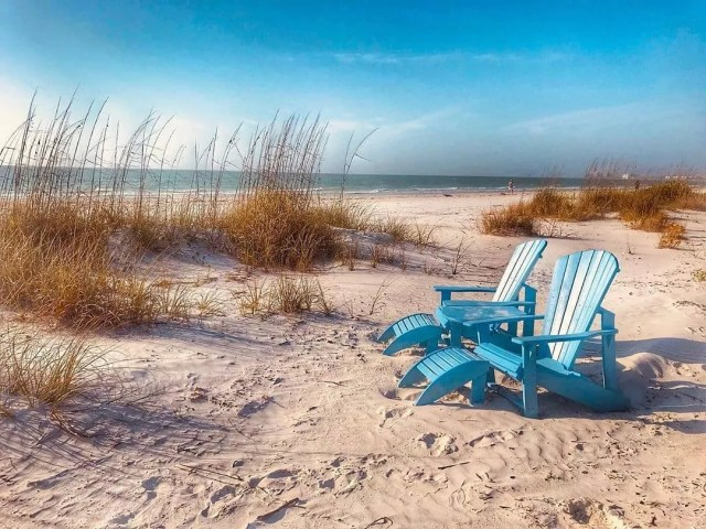 Two Blue Adirondack Chairs on a Beach. Photo by Instagram user @stpetebeach