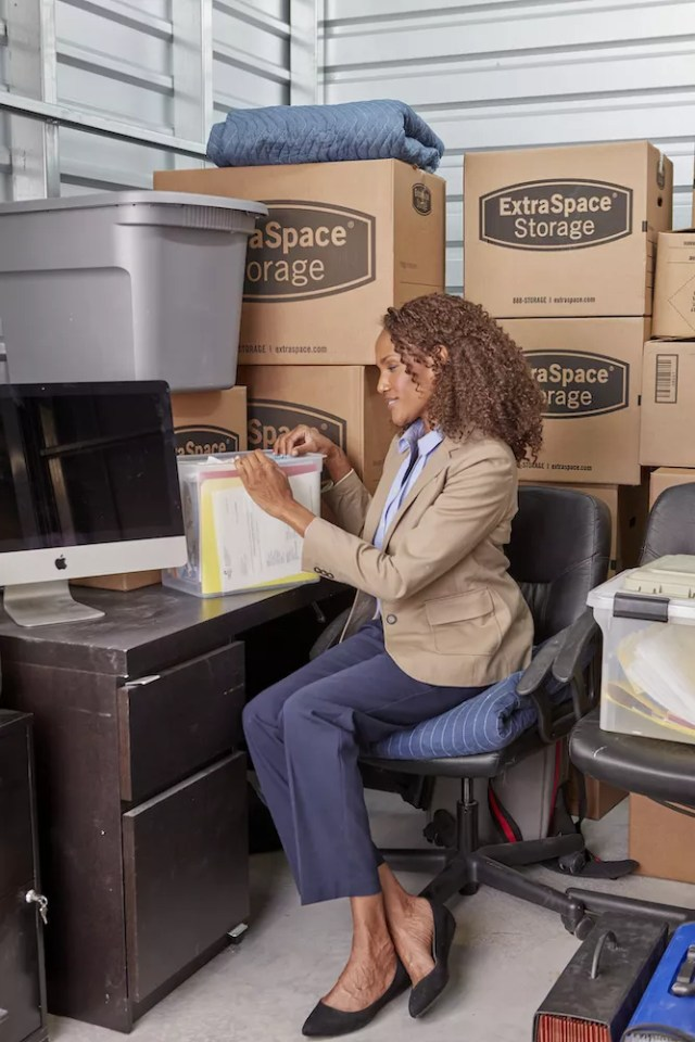 Woman Sitting at a Desk in a Small Storage Unit with Extra Space Storage Boxes Around Her