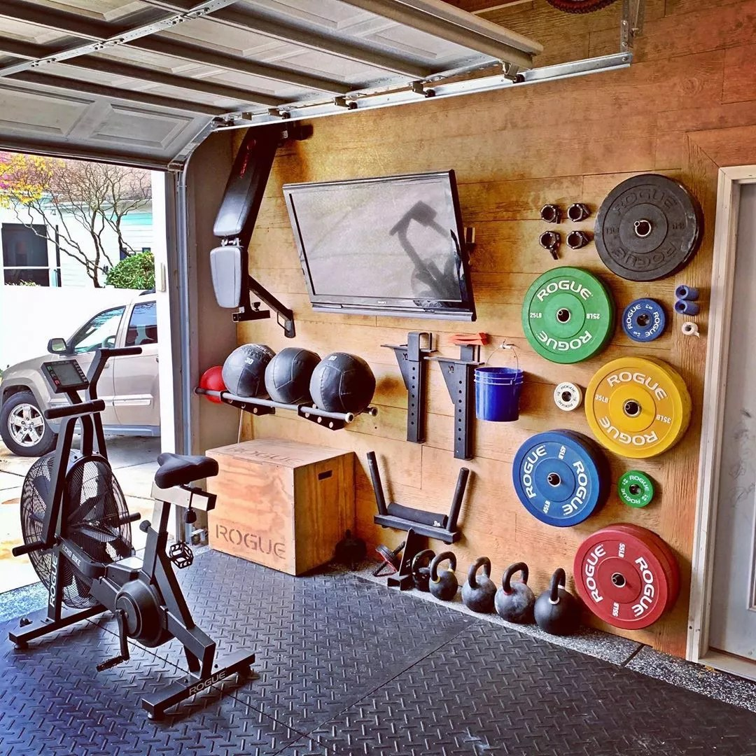 Garage Gym Setup with Weights on the Wall and Assault Air Bike Set Out. Photo by Instagram user @jmlwoodcraft