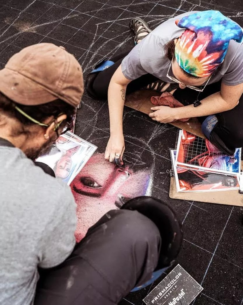 Two People Doing a Chalk Drawing on the Ground. Photo by Instagram user @tempeartfest