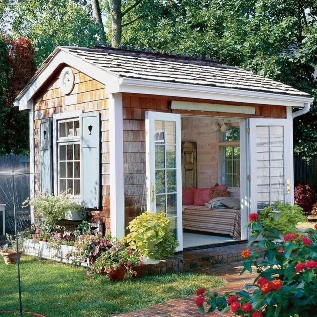 Backyard She Shed with Doors Open and a Small Bed Inside. Photo by Instagram user @sarahellensellschs