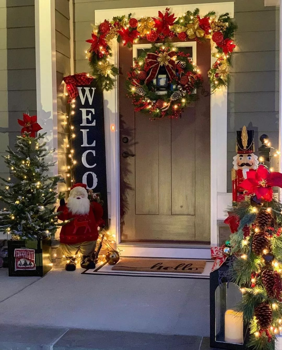 A front porch lights up to reveal a Santa Claus statue on one side of the door, and a nutcracker on the other. Photo by Instagram user @nhomedesignideas.