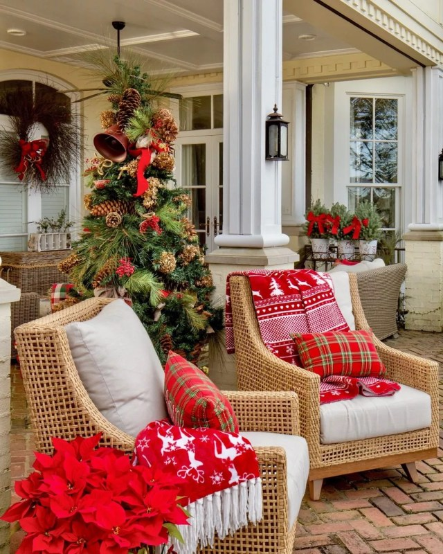 Outdoor furniture chairs have red holiday pillows and a red, white, and green Christmas icon decorated blanket laid over the top of one. Photo by Instagram user @southernladymag.