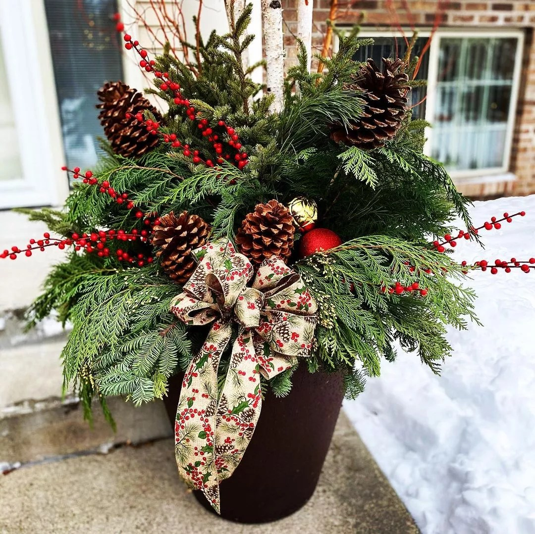 Front porch planter stuffed with pine sprigs, evergreen sprigs, cranberry shoots, pinecones, a large bow, and ornaments. Photo by Instagram user @junealltrades.