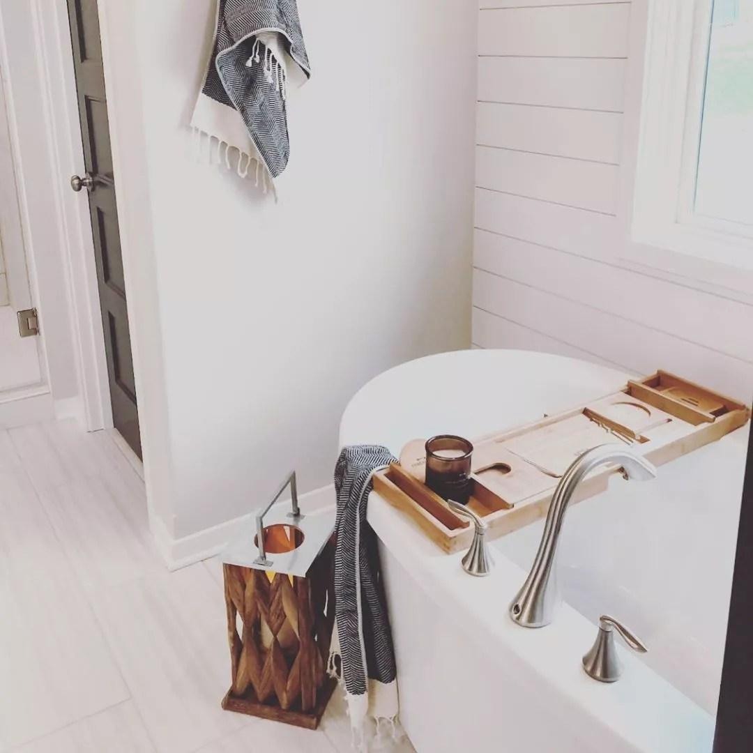 White bathroom with bathtub. Photo by Instagram user @ouralmostlakehouse