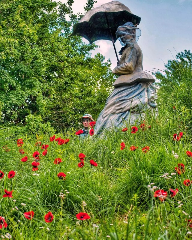 """Statue """"On Poppied Hill"""" by Seward Johnson in Grounds for Sculpture, NJ. Poppies are red and in full bloom amongst long grass and tiny purple flowers. Statue is of a woman in the Victorian era, holding a sun parasol. Photo by Instagram user @thedailyantiquarian"""