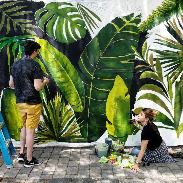 An artist speaking to a helper as she finishes her jungle mural. Photo by Instagram user @ckennylin