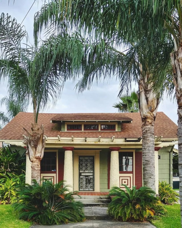 Green bungalow-style home with pillars and palm trees in Fillmore neighborhood. Photo by Instagram user @m.dallemolle