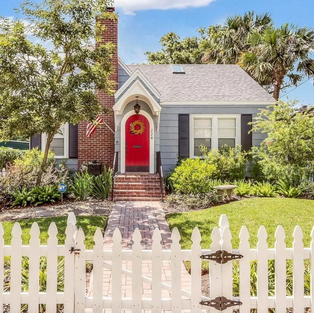 Small Bungalow Home with Red Door and White Picket Fence. Photo by Instagram user @pattypixley