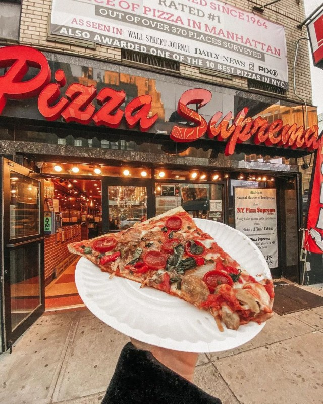 Person Holding a Piece of New York-Style from NY Pizza Suprema. Photo by Instagram user @catcybul