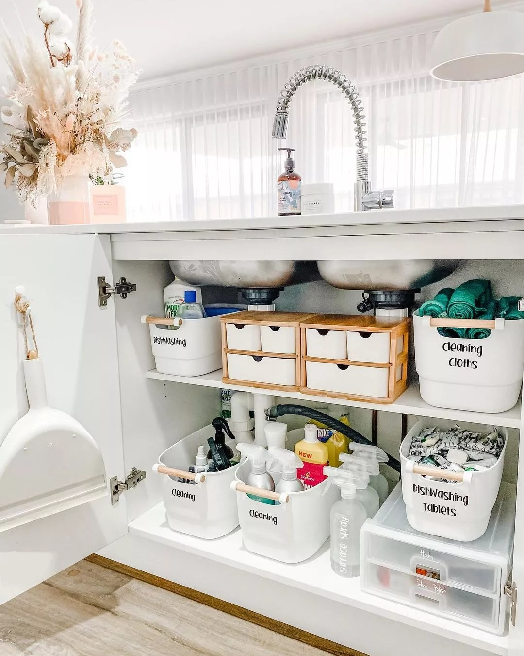 Under sink cabinet organized with shelving and storage bins. Photo by Instagram user @ashleejayinteriors