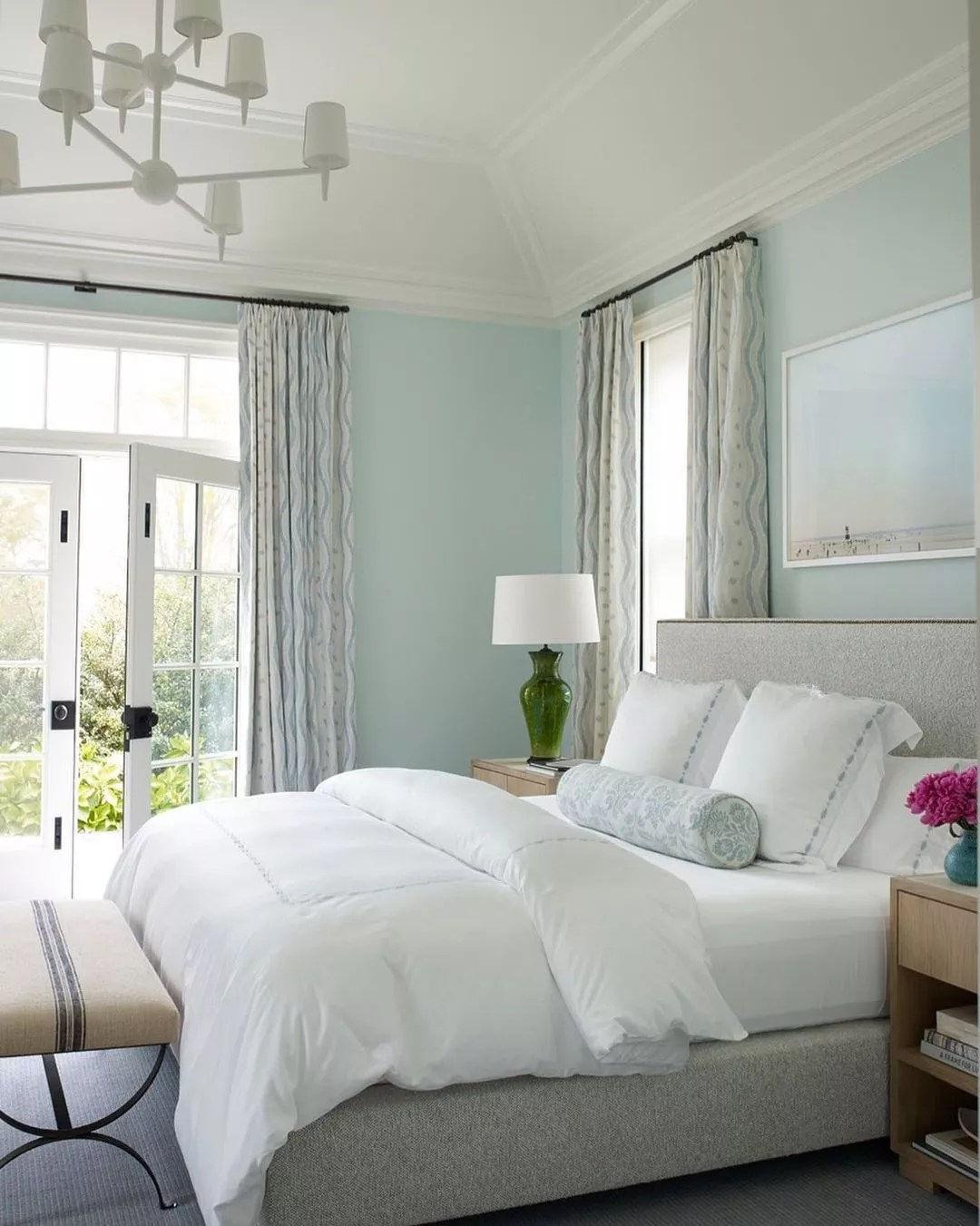 Inviting, white bed in a seafoam-colored bedroom in the Hamptons. Photo by Instagram user @victoriahaganinteriors.