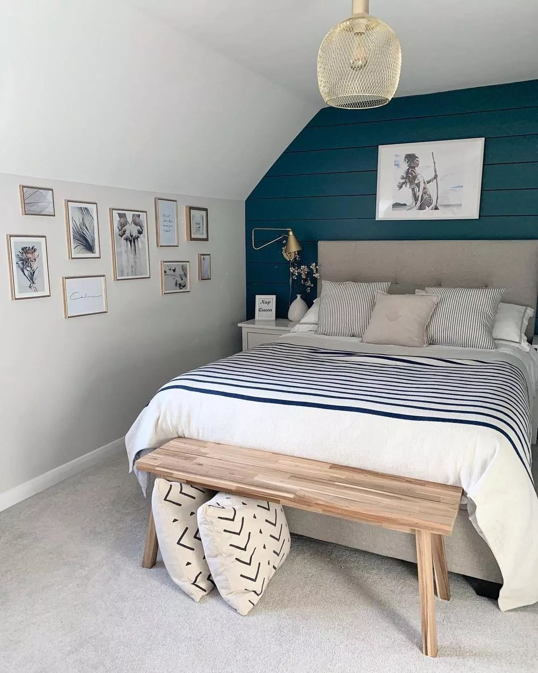White bedroom with dramatic dark teal accent wall. Photo by Instagram user @_homebirds_.