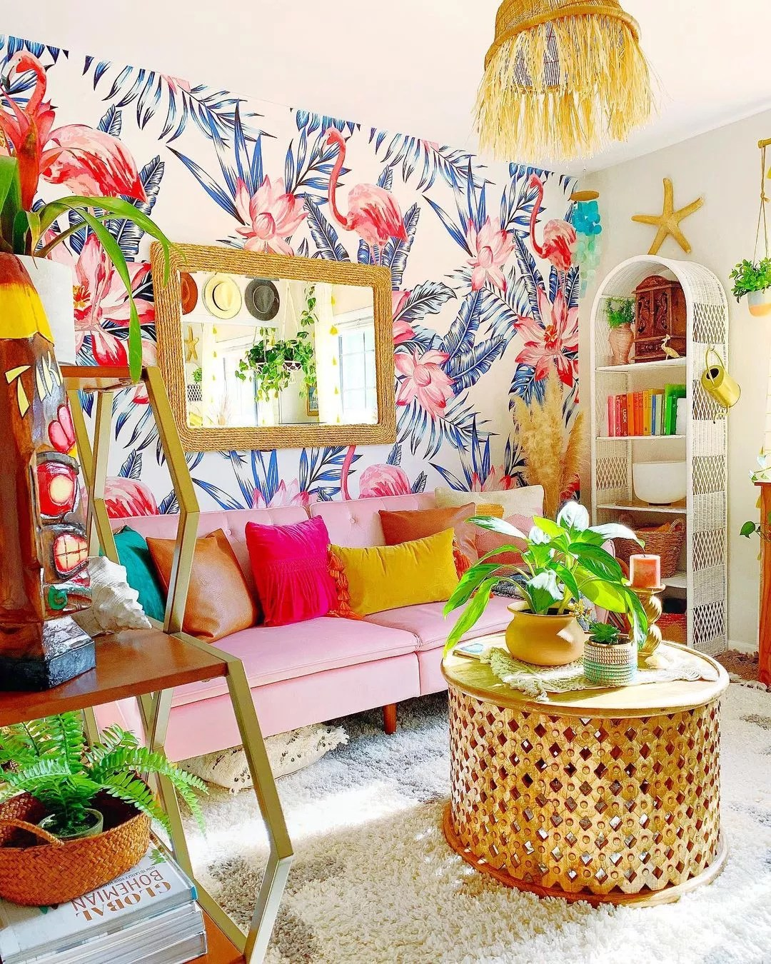 Bright, clean room featuring plants, wall hangings, sofa, rug, and unique statement wallpaper of blue palm leaves, pink waterlilies, and flamingos. Photo by Instagram user @sare_xo_home.
