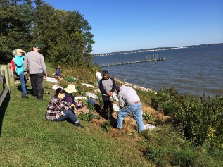 Linda Dodge (seated in plaid shirt), working with Ed Cooper and Larry Brantley planting the hillside garden with funds provided by Unity Gardens overlooking the Severn River.