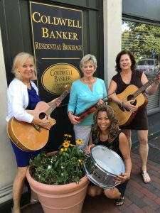 CB Annapolis Church Cir Office Front) – Coldwell Banker Assistant Branch Vice President, Sandra Steward (holding the drum); Coldwell Banker Agent, Ann Chumney (holding guitar left); Coldwell Banker Agent, Ann Englehart (holding guitar right); Coldwell Banker Agent, Patti Moriarty (holding violin).