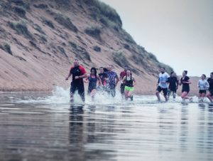 fitness trainer and his clients running in the sea to get fit army style