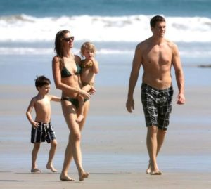 Mother carrying baby walking on the shore with husband and young son in their swimming costumes during the day