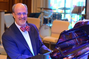 Dr. Gilliland playing piano in a suit