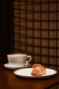 White coffee cup on a table with latte inside, and a white plate on the table with a croissant on it.