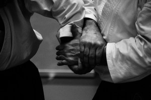 A set of hands grabbing another set in a self defense manner.