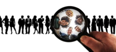 group of people looking down a magnifying glass.