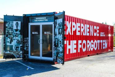 "red shipping container with doors open and ""experience the forgotten"" on the side"