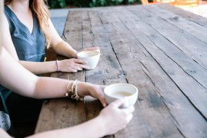 two set of hands holding white mugs on a table.
