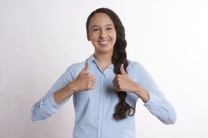 young caucasian woman in light vlue button up with side braid and both thumbs up.