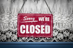 """red sign with """"sorry we're closed"""" in white"""
