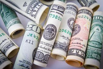 different money bills rolled up