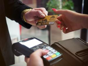 caucasian hand handing another hand a gold credit card